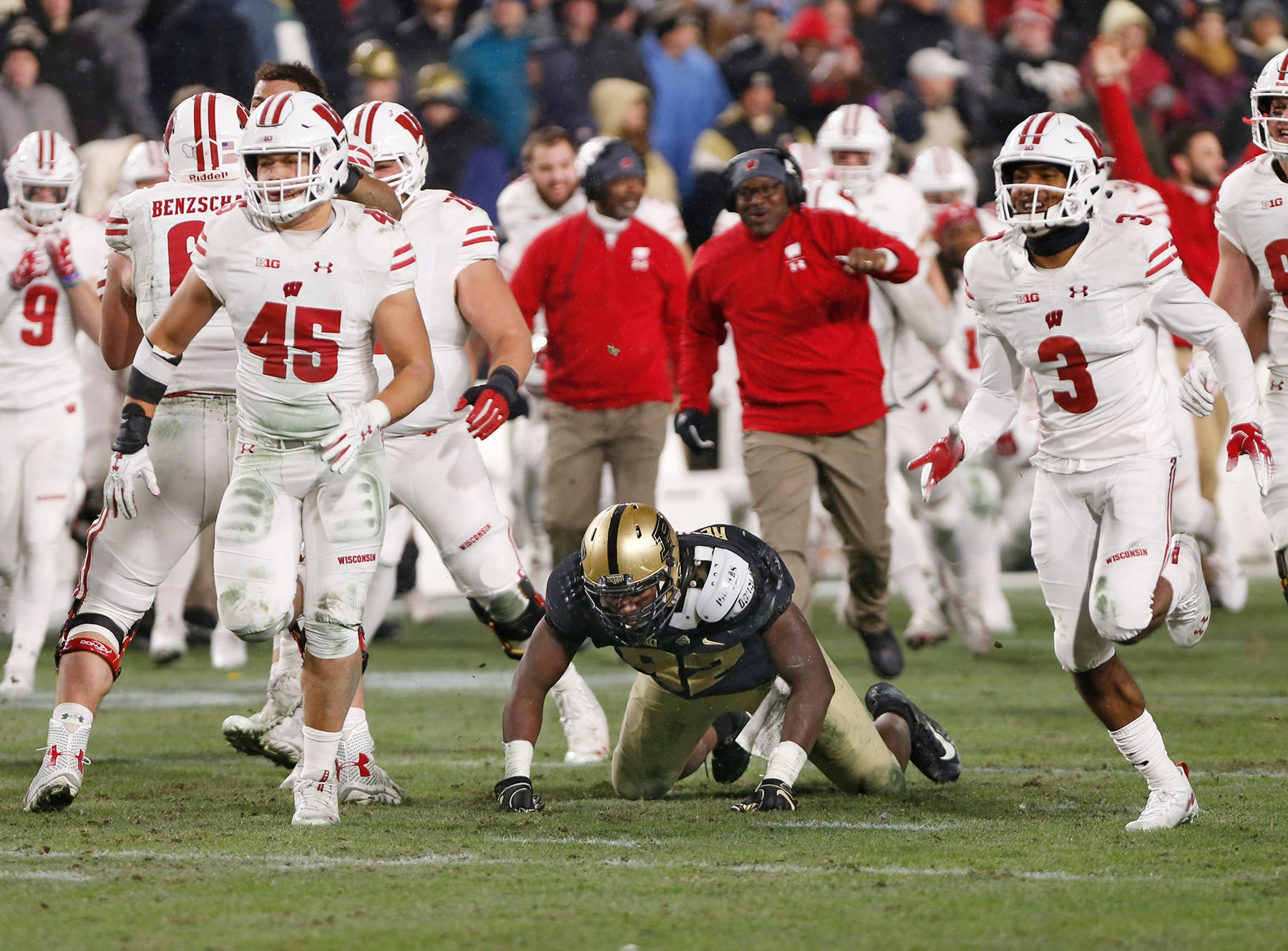 Giovanni Reviere of Purdue slumps to his knees as Wisconsin players rush the field following Jonathon Taylor's winning touchdown in the third overtime period Saturday, November 17, 2018, at Ross-Ade Stadium. Purdue fell to Wisconsin 47-44 3OT.