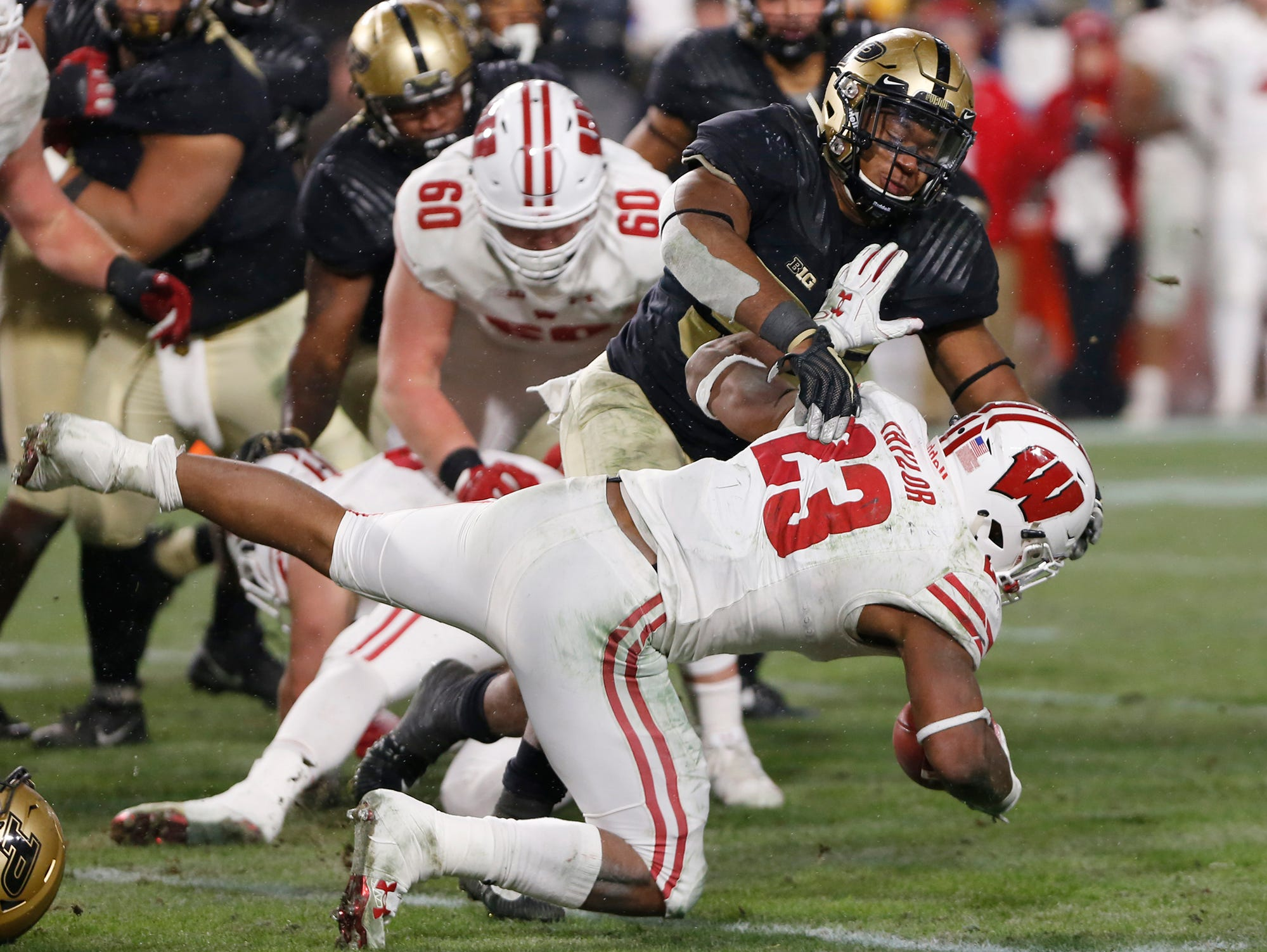Derrick Barnes of Purdue brings down Jonathan Taylor of Wisconsin in the fourth quarter Saturday, November 17, 2018, at Ross-Ade Stadium. Purdue fell to Wisconsin 47-44 3OT.