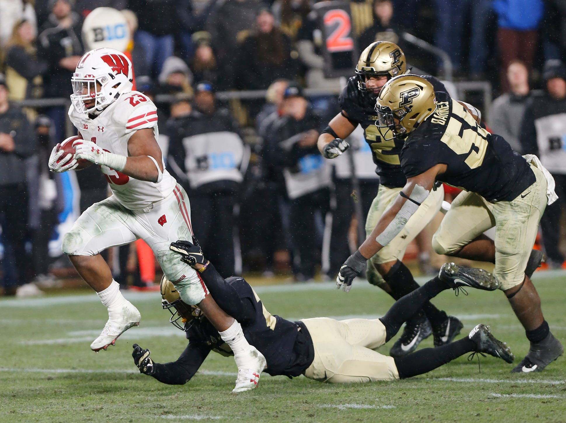 Jonathon Taylor of Wisconsin slips through the grasp of Navon Mosley of Purdue as he rushes for the winning touchdown in the third overtime period Saturday, November 17, 2018, at Ross-Ade Stadium. Purdue fell to Wisconsin 47-44 3OT.