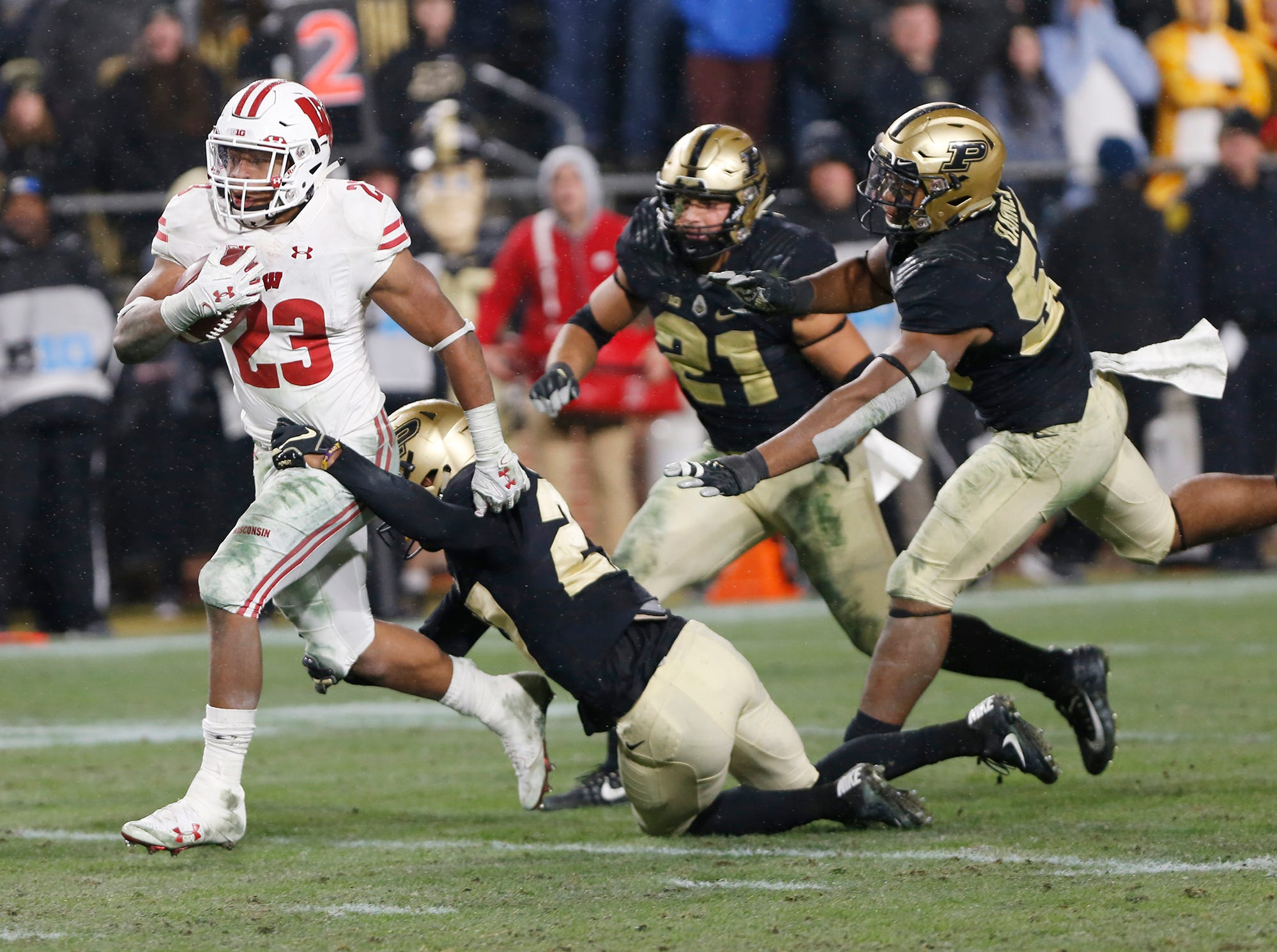 Jonathan Taylor of Wisconsin slips through the grasp of Navon Mosley of Purdue as he rushes for the winning touchdown in the third overtime period Saturday, November 17, 2018, at Ross-Ade Stadium. Purdue fell to Wisconsin 47-44 3OT.