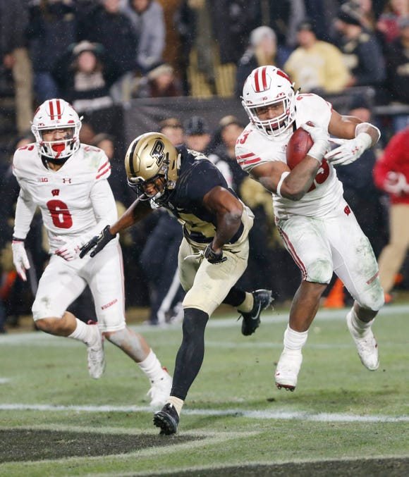 Jonathan Taylor of Wisconsin runs over Antonio Blackmon of Purdue as he rushes for the winning touchdown in the third overtime period Saturday, November 17, 2018, at Ross-Ade Stadium. Purdue fell to Wisconsin 47-44 3OT.