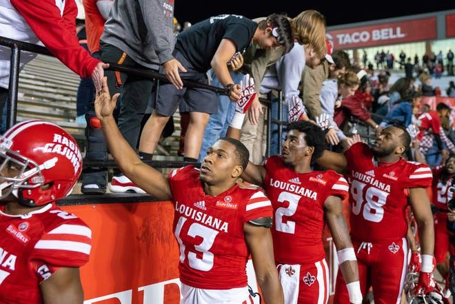 Before turning their attention to this week's visit to UL Monroe, Ragin' Cajuns Ryheem Malone (13), Ja'Marcus Bradley (2) and LaDarrius Kidd (98) celebrate with fans after UL's 48-38 win over South Alabama on Saturday night at Cajun Field.