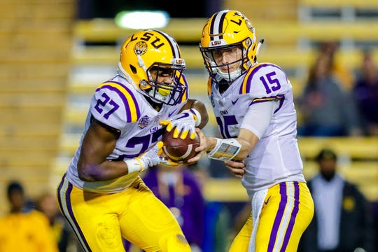 LSU Tigers quarterback Myles Brennan (15) hands the ball off to running back Lanard Fournette (27) during Saturday's game against Rice at Tiger Stadium.