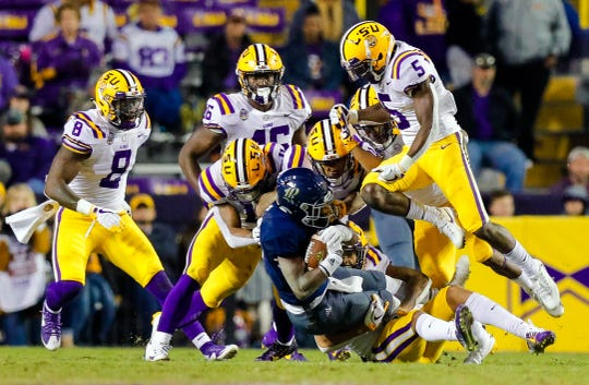 Rice wide receiver Austin Conrad (12) is brought down by a host of LSU tacklers led by Kary Vincent Jr. (5) during Saturday's game in Baton Rouge.