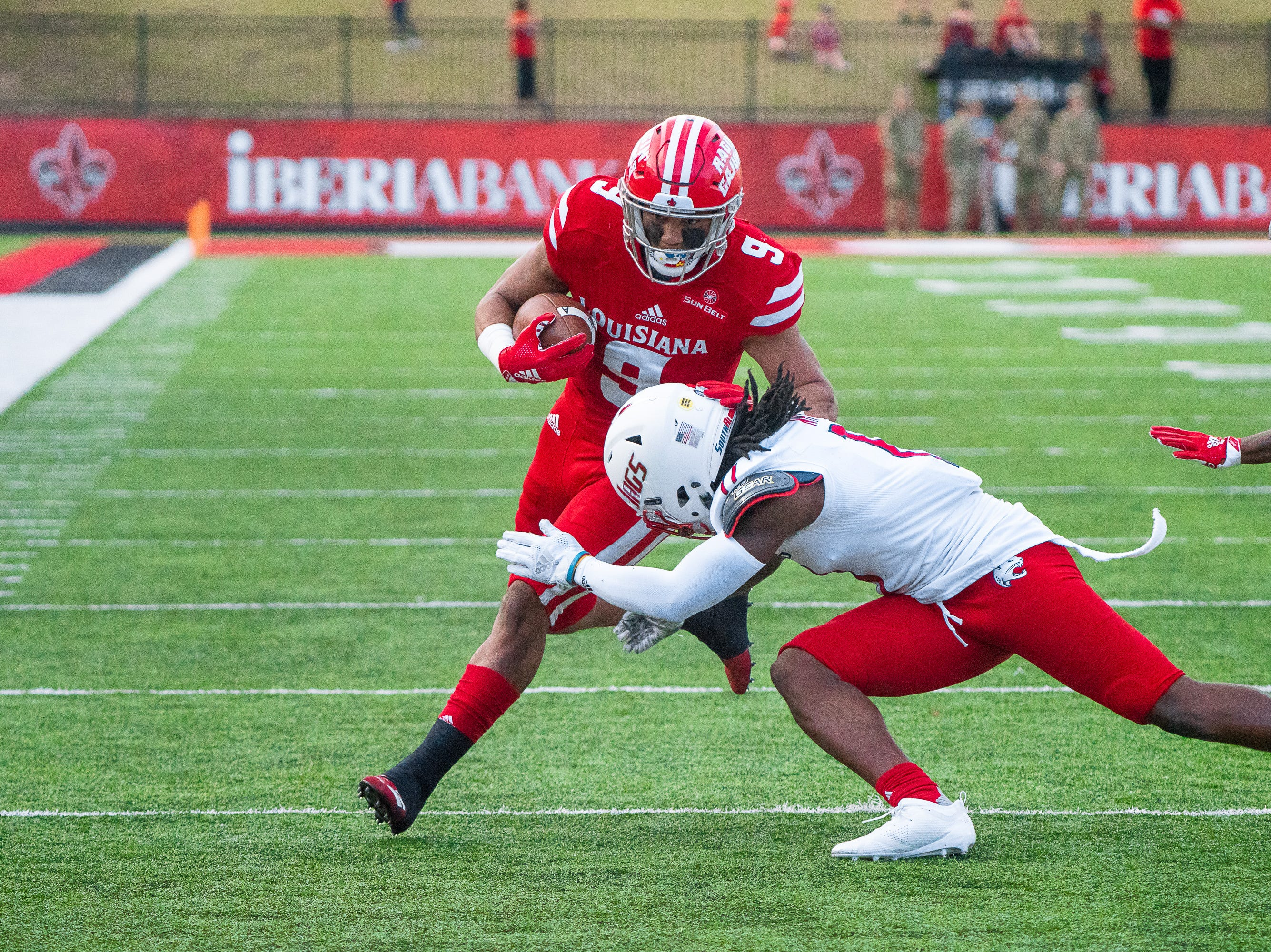 UL's Trey Ragas charges through a defender while running the ball as the Ragin' Cajuns play against the South Alabama Jaguars at Cajun Field on November 17, 2018.