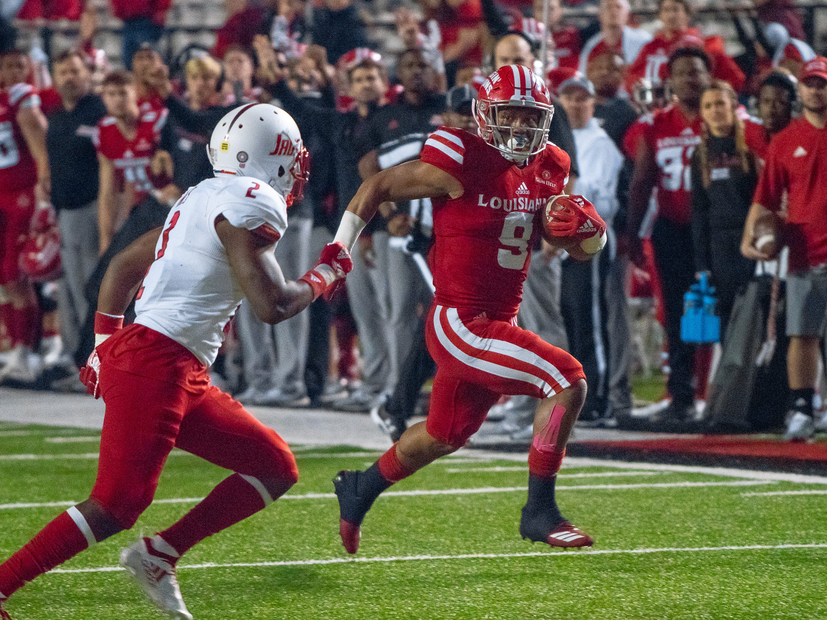 UL's Trey Ragas watches his defender while running the ball down the field as the Ragin' Cajuns play against the South Alabama Jaguars at Cajun Field on November 17, 2018.
