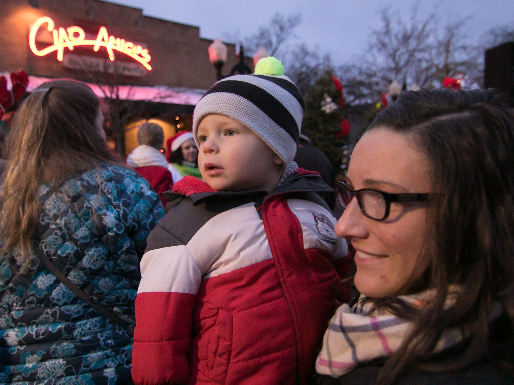 19-month-old Jude Pearson, held by friend Noelle Mancuso, watches the minature train with fascination Saturday, Nov. 17, 2018 at the Holiday Glow.