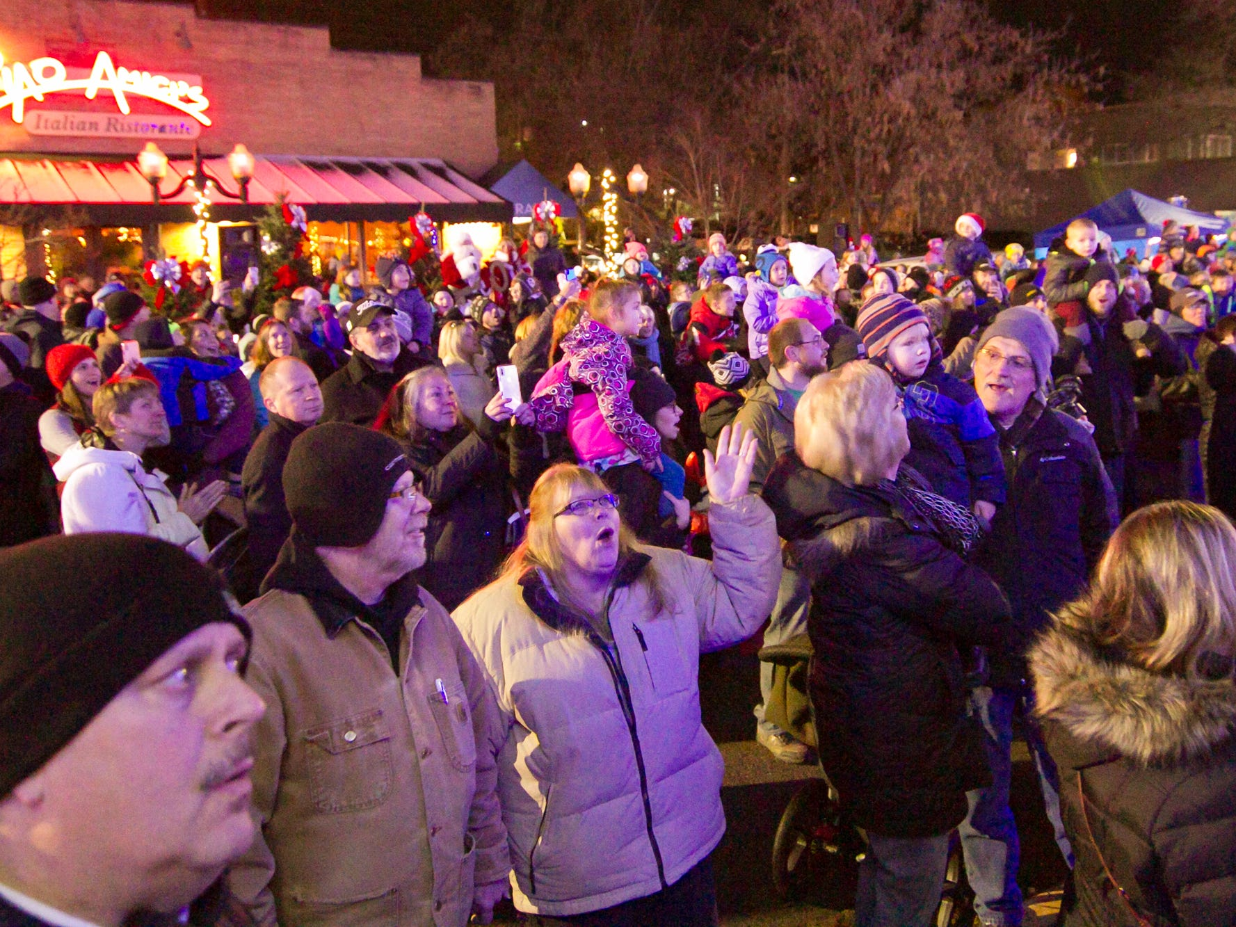 After Santa Claus signals the lighting of the Christmas tree and other lights in trees along the Mill Pond, the crowd reacts to the lighting with awe Saturday, Nov. 17, 2018 at Brighton's Holiday Glow.