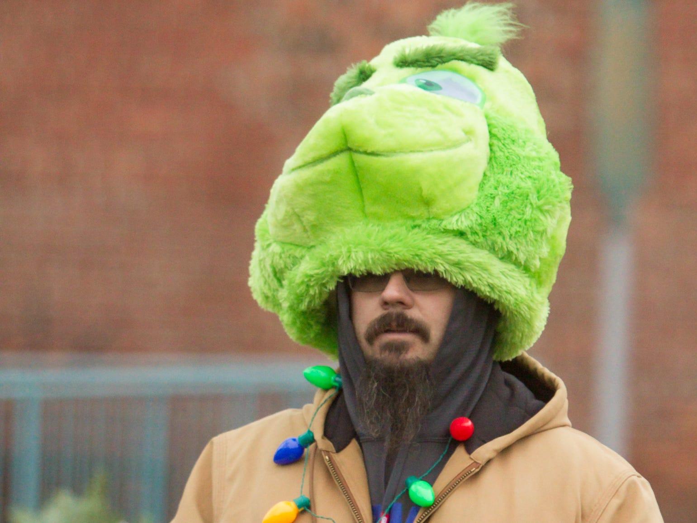 Robert Egenolf of Brighton puts on his Grinch hat for Brighton's Holiday Glow Saturday, Nov. 17, 2018.