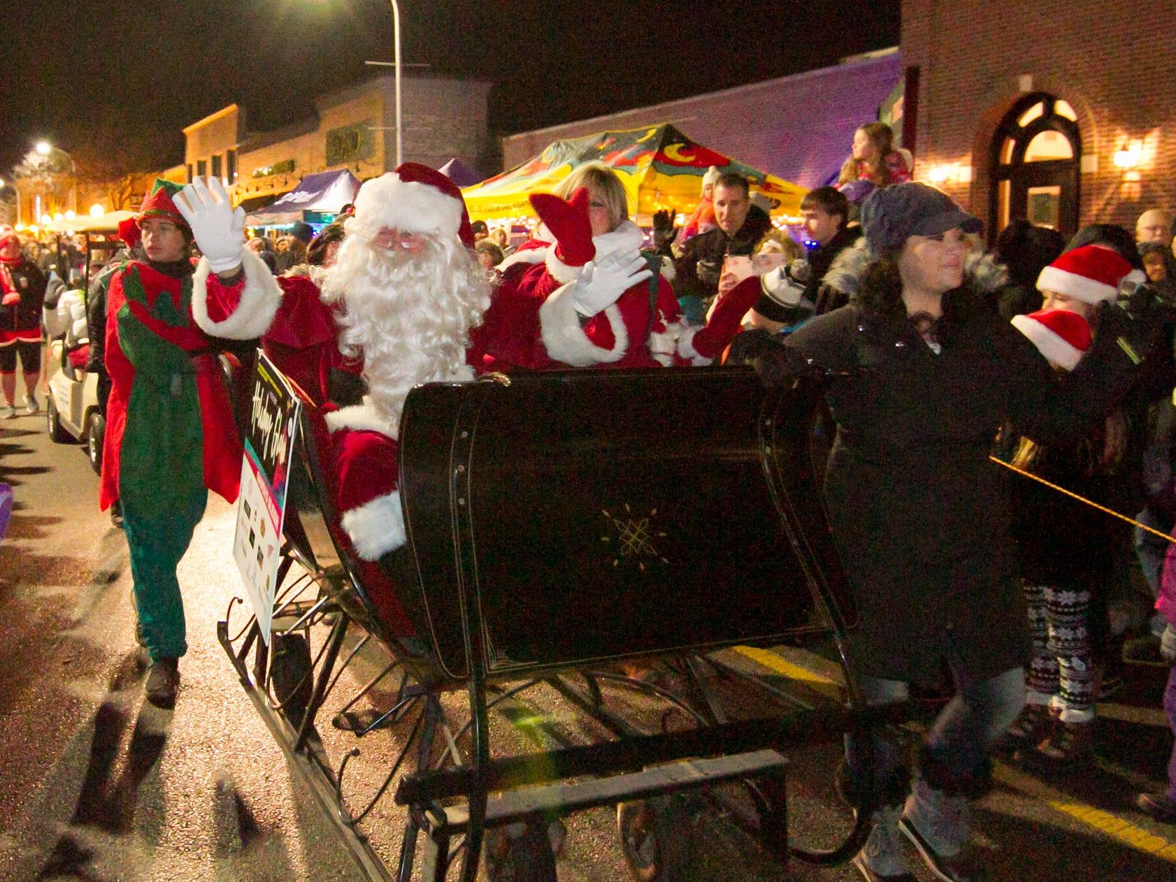 "Santa and Mrs. Claus wave to a crowd who earlier had chanted ""Santa, Santa"" in anticipation of his arrival at Brighton's Holiday Glow Saturday, Nov. 17, 2018."