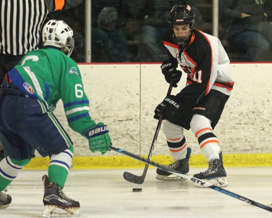 Brighton's Noah Stanko (11) stickhandles the puck while being defended by Saginaw Heritage's Joseph Watson on Saturday, Nov. 17, 2018.