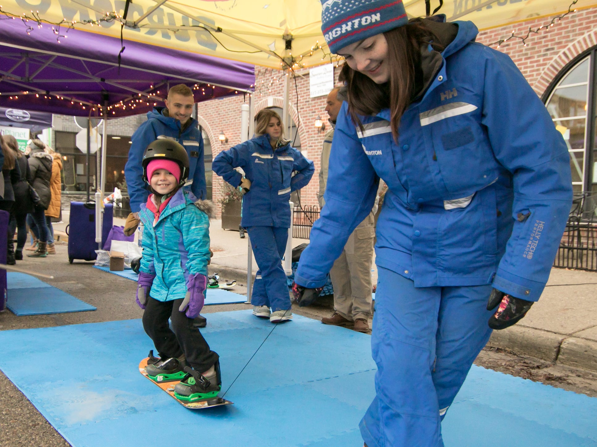 7-year-old Lauren Kirila gets a feel for snowboarding, pulled by Mt. Brighton ski instructor Erin McGill at the Holiday Glow Saturday, Nov. 17, 2018.