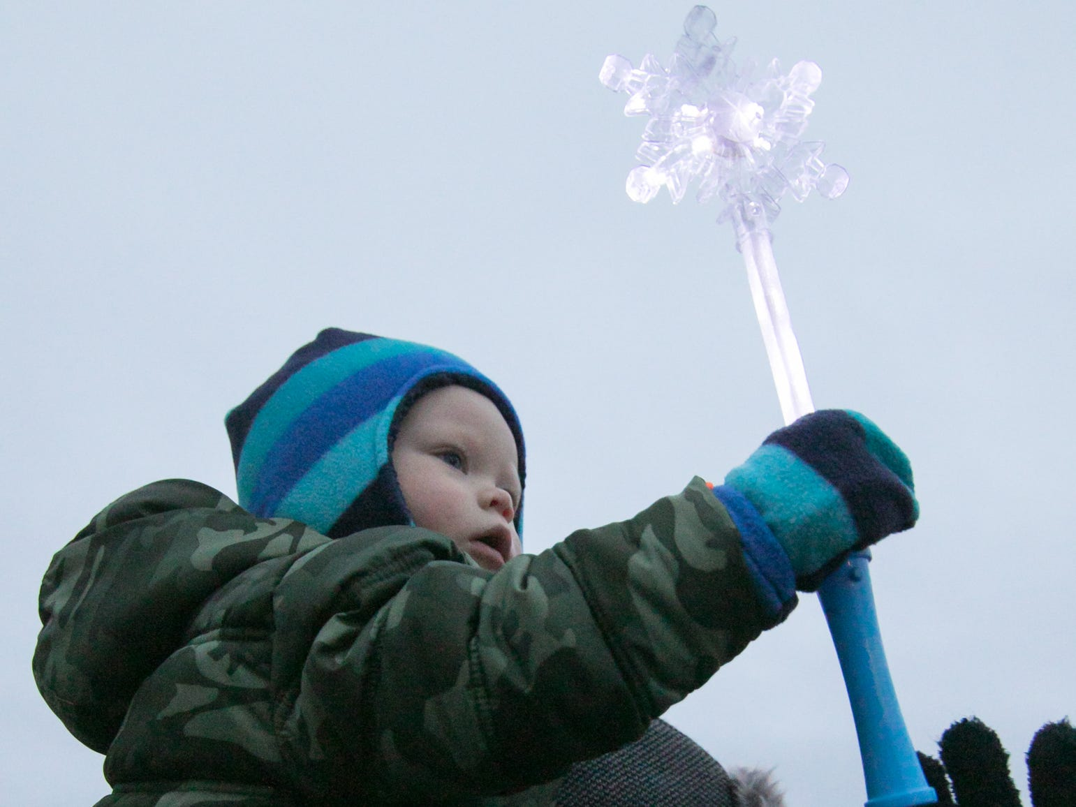 17-month-old Benjamin Hornyak sits on his dad Billy's shoulders, fascinated by a glowing snowflake wand at the Holiday Glow Saturday, Nov. 17, 2018.
