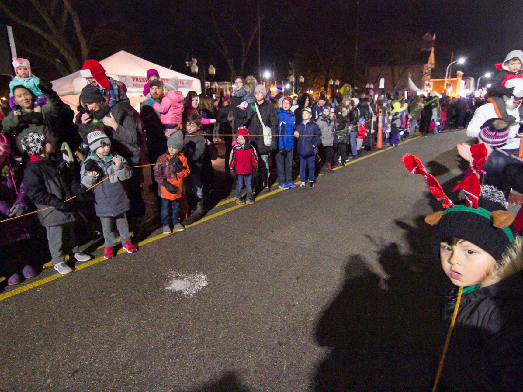 People line a roped-off path set up for the arrival of Santa Claus, who would be pulled by reindeer down Main Street in Brighton's Holiday Glow Saturday, Nov. 17, 2018.