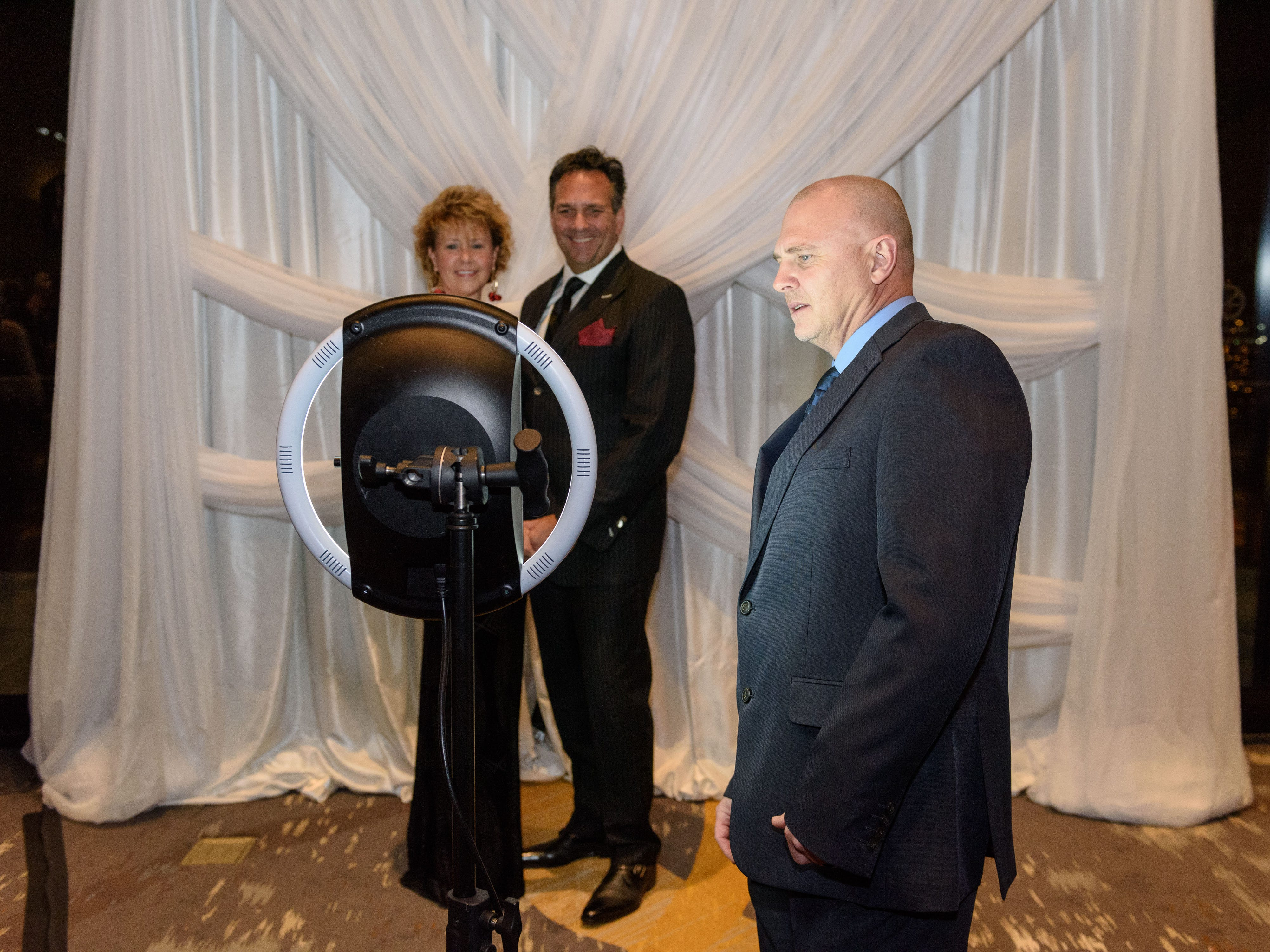 Mitzi and Steve Tomanchek pose for a photo as David Head assists at the Snow Ball Gala at the Omni Hotel, a benefit for the Jennifer Lawrence Cardiac Intensive Care Unit (CICU) at Norton ChildrenÕs Hospital. Nov. 17, 2018