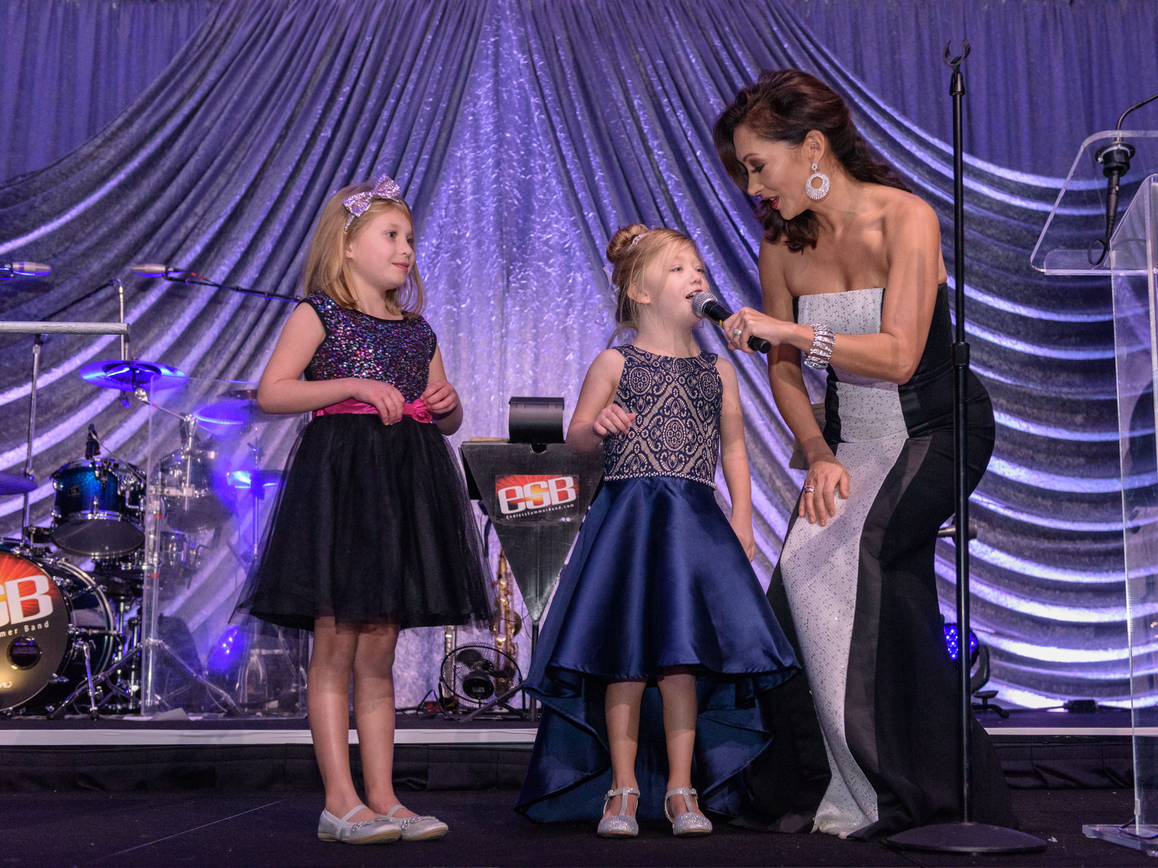 Shannon Cogan of WAVE 3 holds the microphone as Rosie Bowling and Lilly Brown tells everyone to get their raffle tickets in before the drawing at the Snow Ball Gala at the Omni Hotel, a benefit for the Jennifer Lawrence Cardiac Intensive Care Unit (CICU) at Norton ChildrenÕs Hospital. Nov. 17, 2018