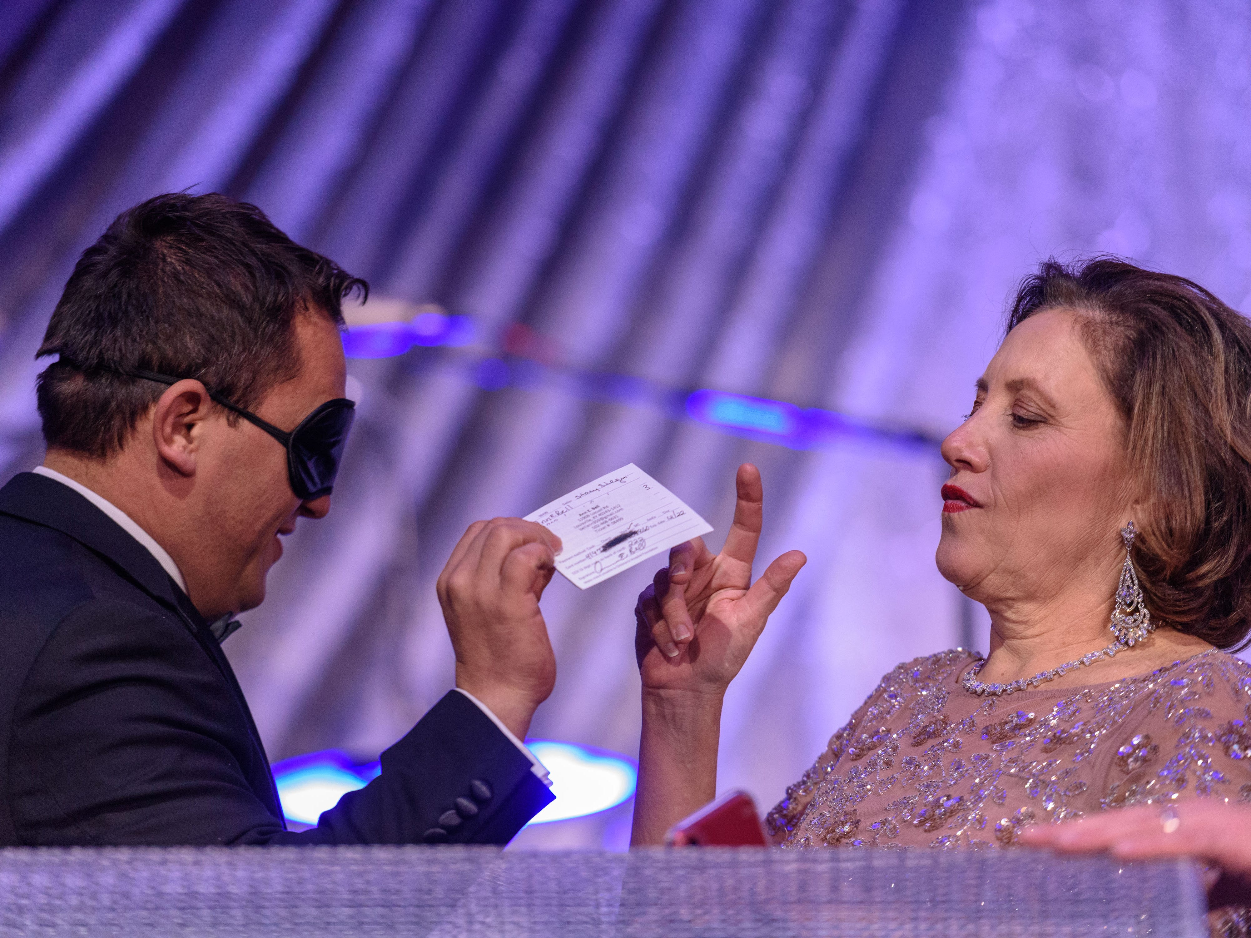 AdrianÊMiron draws the first winner for a 2019 BMW 2 Series convertible with $10,000 cash, Ann E. Bell, and gives it to Lynnie Meyer, Ed.D, Chief Development Officer, Norton Healthcare, at the Snow Ball Gala at the Omni Hotel, a benefit for the Jennifer Lawrence Cardiac Intensive Care Unit (CICU) at Norton ChildrenÕs Hospital. Nov. 17, 2018