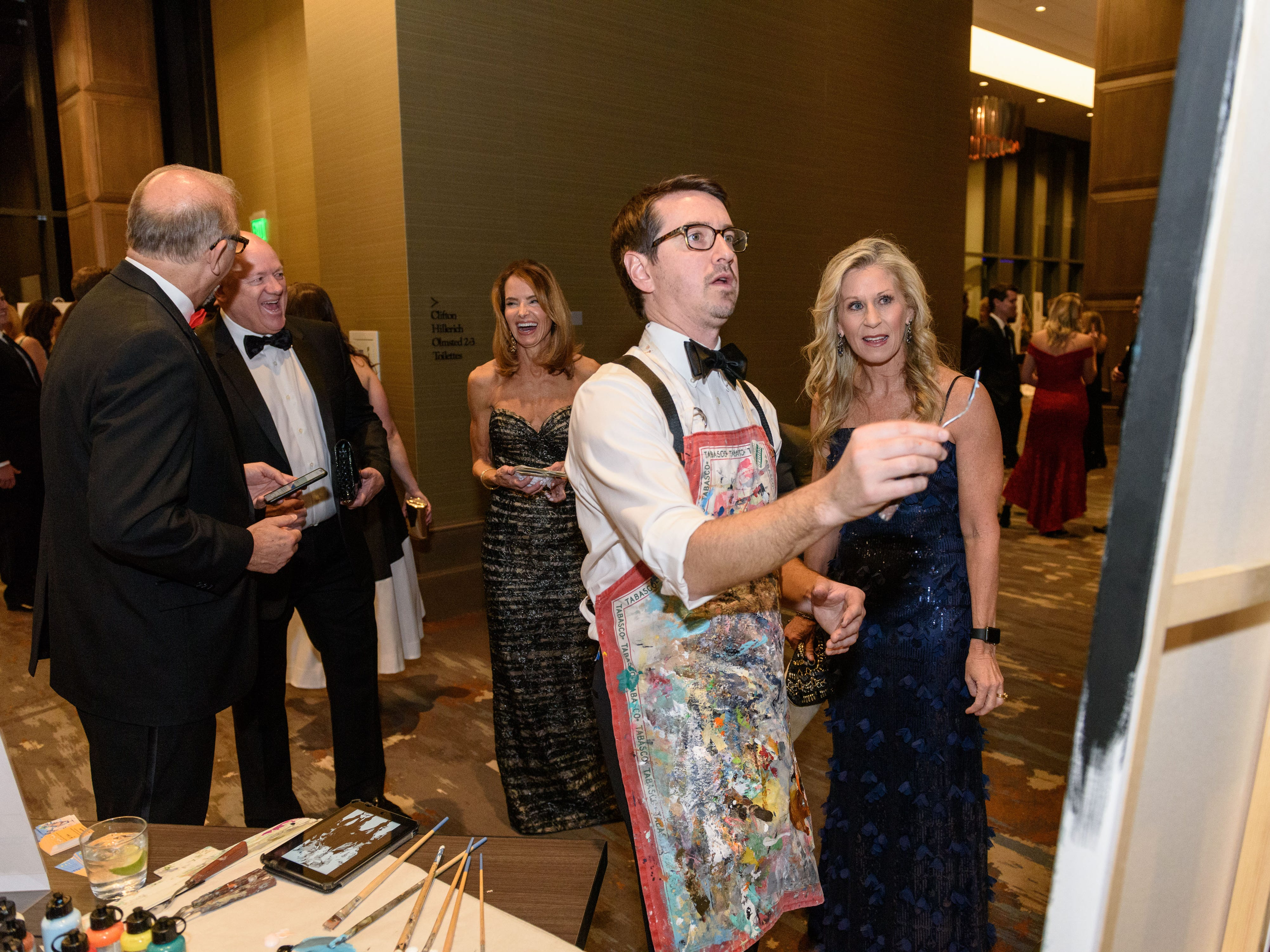 """Artist Tyler Robertson works on """"Changing Leads,"""" as guests pass by at the Snow Ball Gala at the Omni Hotel, a benefit for the Jennifer Lawrence Cardiac Intensive Care Unit (CICU) at Norton ChildrenÕs Hospital. Nov. 17, 2018"""