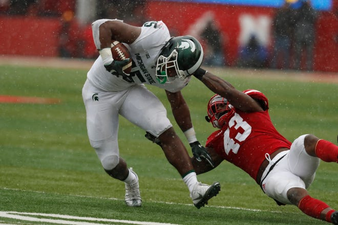 Michigan State's La'Darius Jefferson tries to pull away from Nebraska linebacker Tyrin Ferguson during the second half on Saturday. Jefferson carried seven times for 16 yards.