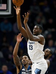 The Grizzlies' Jaren Jackson Jr. (13) passes the ball away from the Timberwolves' Jeff Teague, left, and Andrew Wiggins during the first quarter Sunday.