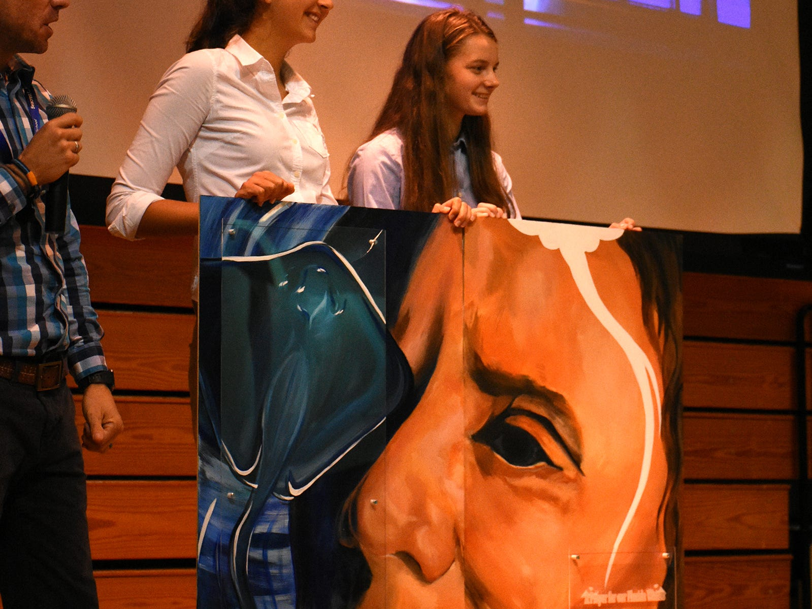 Student artists Jordan Corina, from left, and Hadley Wimsatt presented a painting of Dr. Earle to her after her talk.  Seacrest Country Day School students heard from a renowned oceanographer, and she heard from them, when Dr. Sylvia Earle visited the Naples preparatory school for a presentation and workshops on Wednesday, Nov. 14.