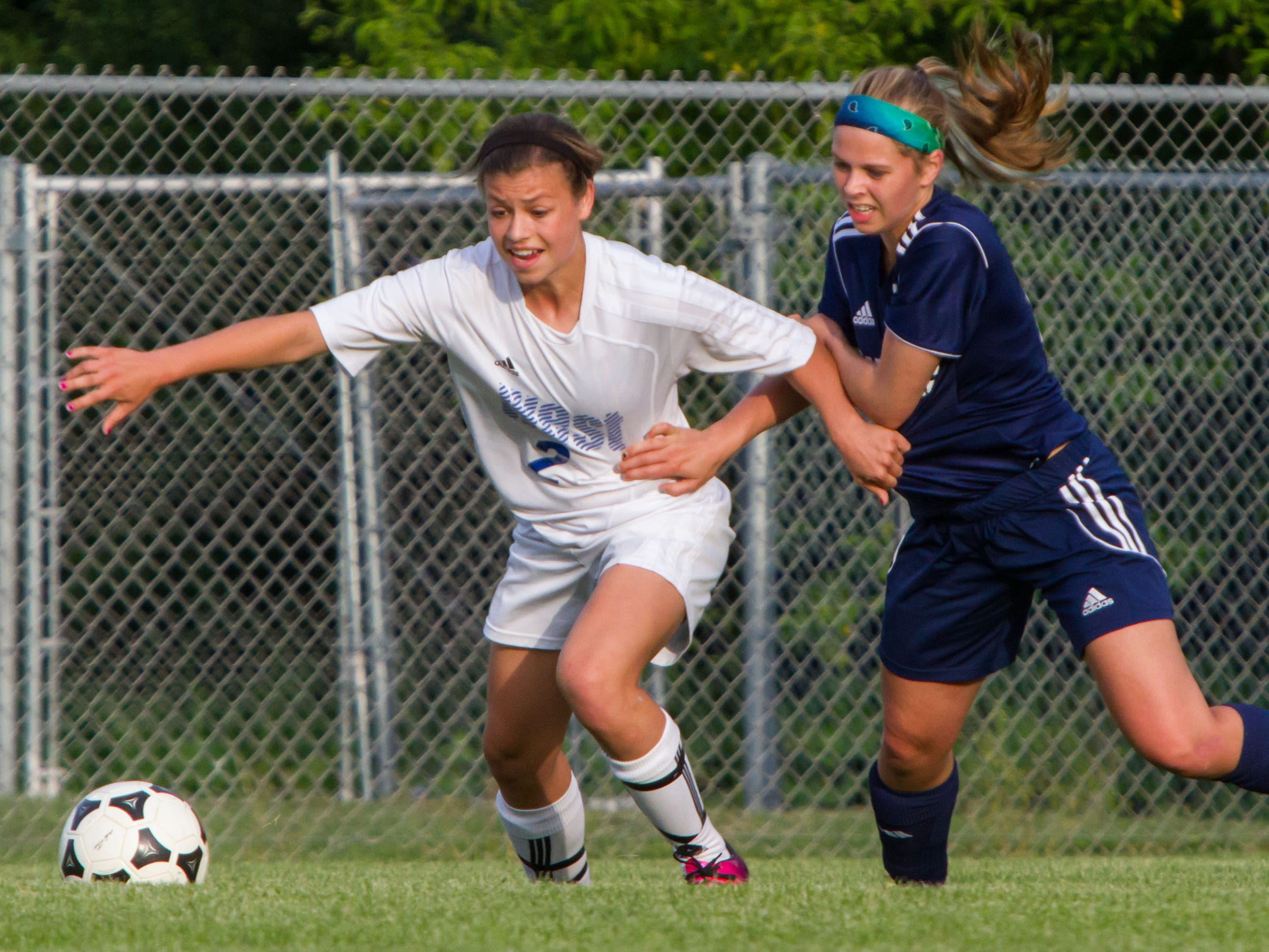Waukesha West freshman Dani Rhodes (left) and Kettle Moraine junior Hannah McIntosh battle for possession during the sectional final match at Kettle Moraine on Saturday, June 8, 2013.