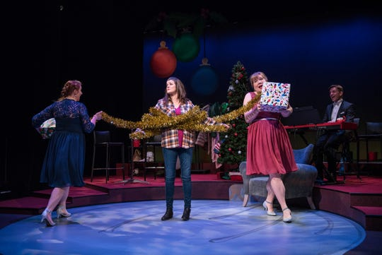 """Marcee Doherty-Elst (left) and Kelly Doherty (right) wind a garland around Susie Duecker (center) in """"The Twelve Dates of Christmas"""" at Next Act Theatre."""