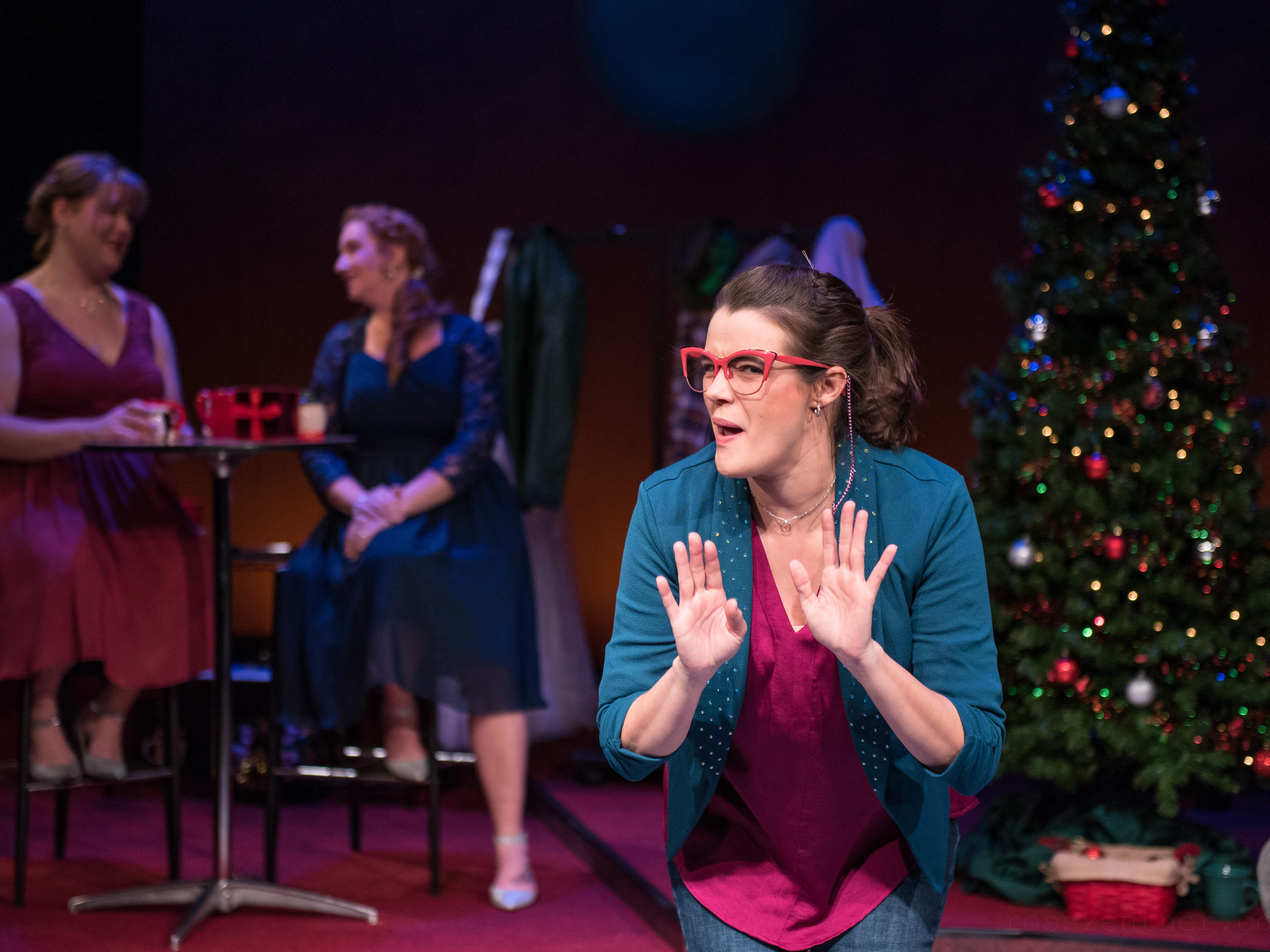 "Kelly Doherty (left) and Marcee Doherty-Elst shmooze while Susie Duecker (right) imitates a relative in ""The Twelve Dates of Christmas"" at Next Act Theatre."