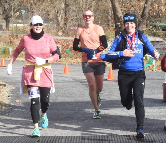 Craig Adams (middle) of Bentonville crosses the finish line to win last year's White River Marathon for Kenya in Cotter.