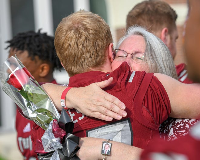 Troy senior Hunter Reese and Mary Lou McCullers, mother of the late Corey McCullers, hug before Saturday's game.