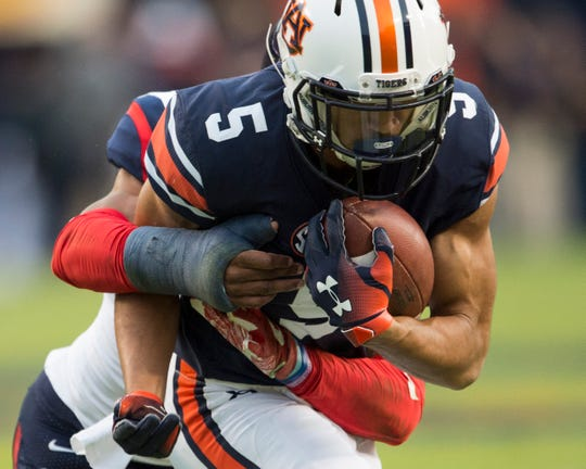 Auburn wide receiver Anthony Schwartz (5) is wrapped up by Liberty defensive back Jeremy Peters (2) at Jordan-Hare Stadium in Auburn, Ala., on Saturday, Nov.. 17, 2018. Auburn defeated Liberty 53-0.