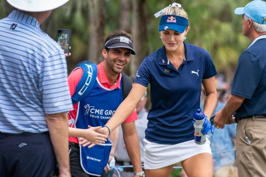 Lexi Thompson exchange highfives with a young fan as she walks up to the last 18th tee during the last round of LPGA season-ending CME Championship at Tiburón Golf Club in Naples, Florida Sunday, November 18, 2018. Florida native, Lexi Thompson wins the game with 18 under par.
