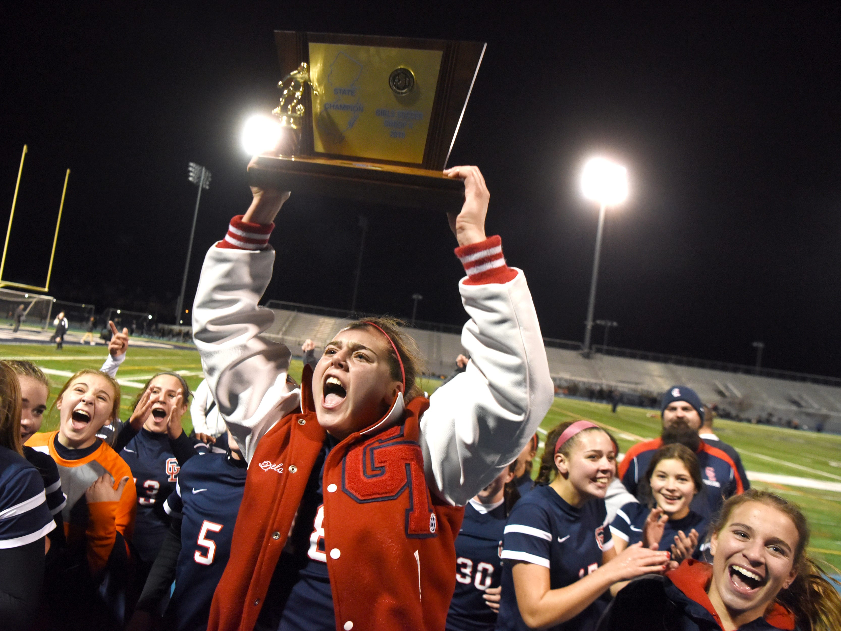Governor Livingston's Claire Donfield hoists the Group II trophy while celebrating with teammates on Sunday, Nov. 18, 2018 at Kean University.