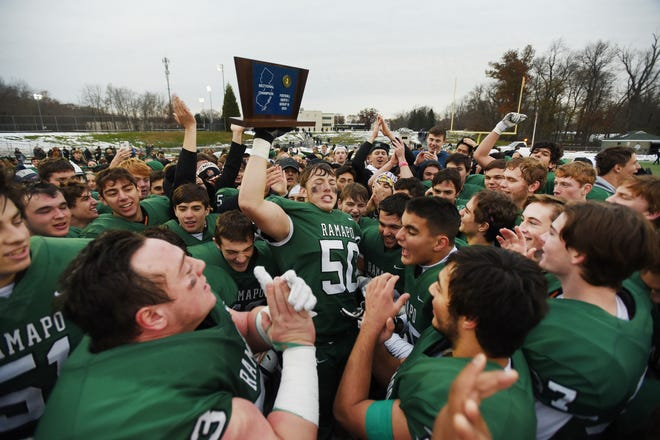 Sean Costello (no. 50) holds up the Championship Plaque as  Ramapo players celebrate their championship victory 31 to 7 over River Dell in the second half during the North 1, Group 3 football final at Ramapo High School in Franklin Lakes on 11/18/18.