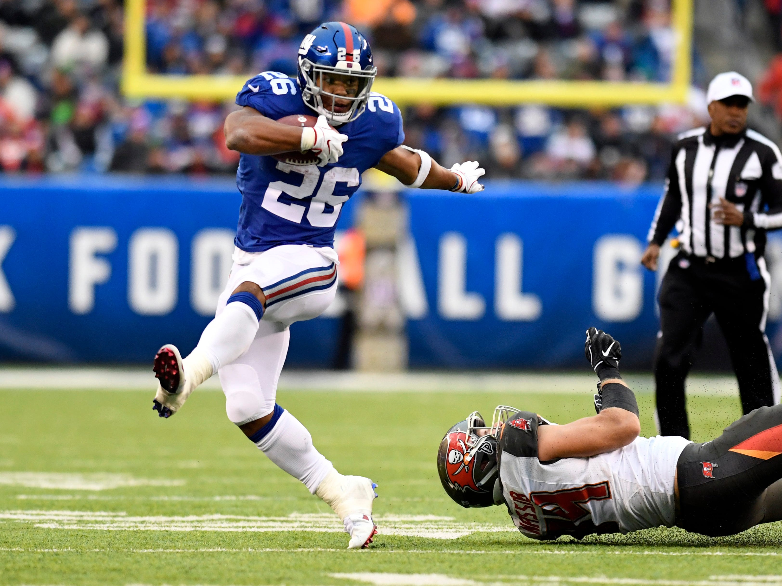 New York Giants running back Saquon Barkley (26) breaks a Tampa Bay Buccaneer tackle in the second half. The Giants defeat the Buccaneers 38-35 on Sunday, Nov. 18, 2018 in East Rutherford.