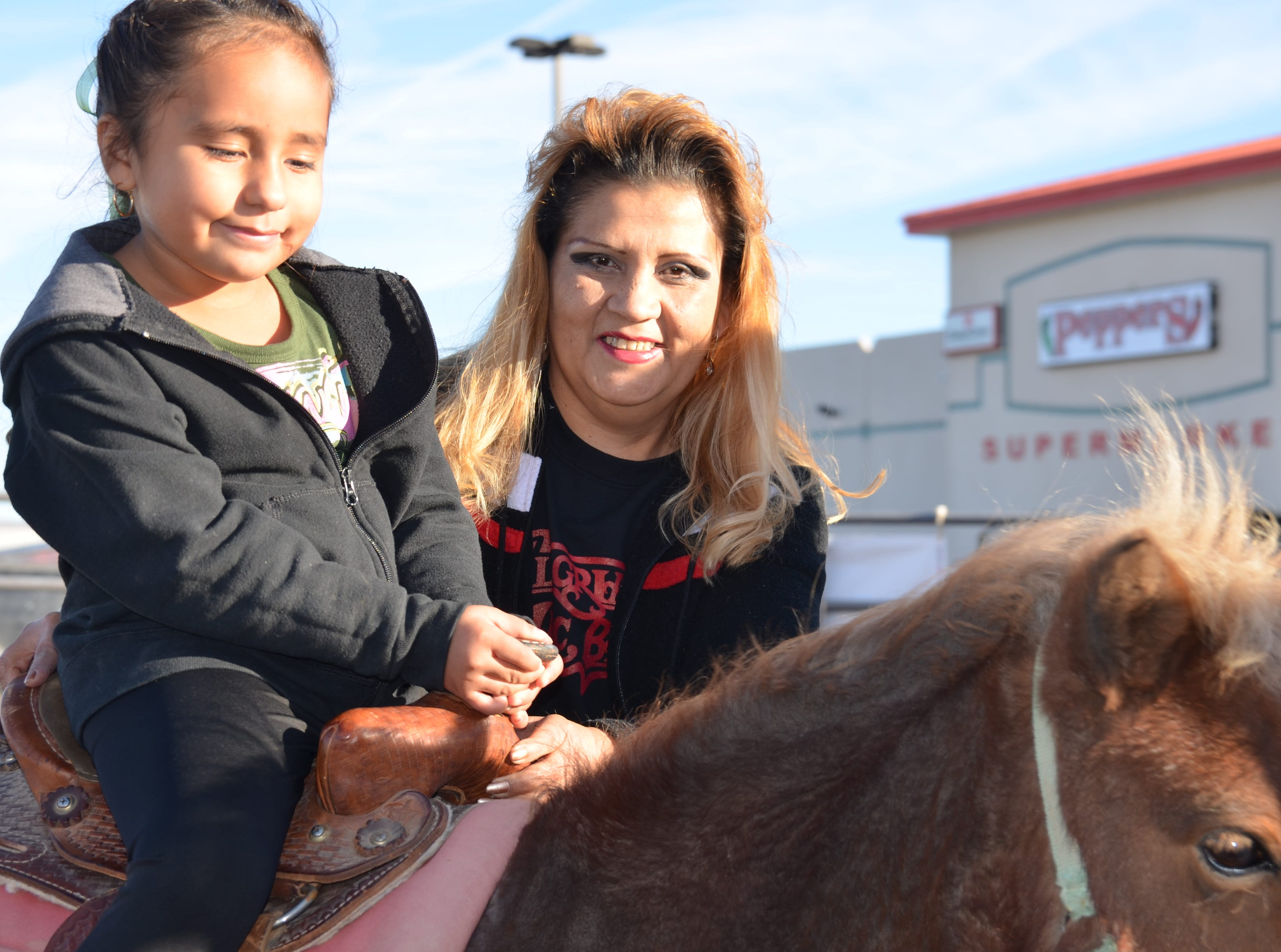 Ruby Marie Luera, 6, rides a pony while her mother, Josie Luera secures her ride.