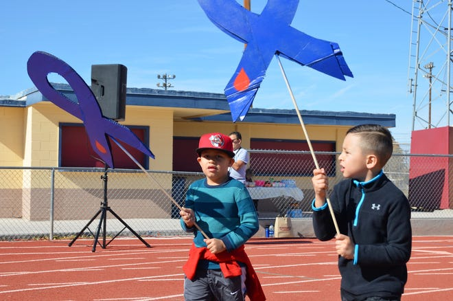 Axel Lozoya, 6, and Ayden Galvan, 7, hold blue ribbon placards to show their support against diabetes during a recent fundraising walk in Deming.