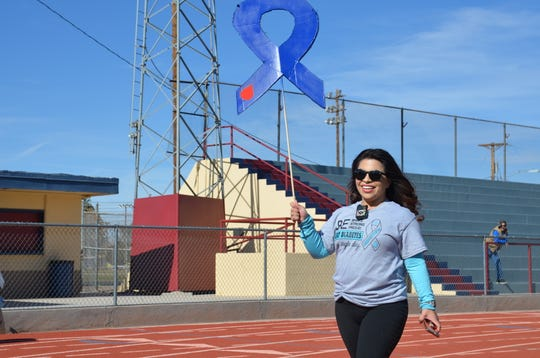 Johanna Quintana, organizer of Luna County Fight Diabetes 2-mile walk proudly walks with her blue ribbon placard.