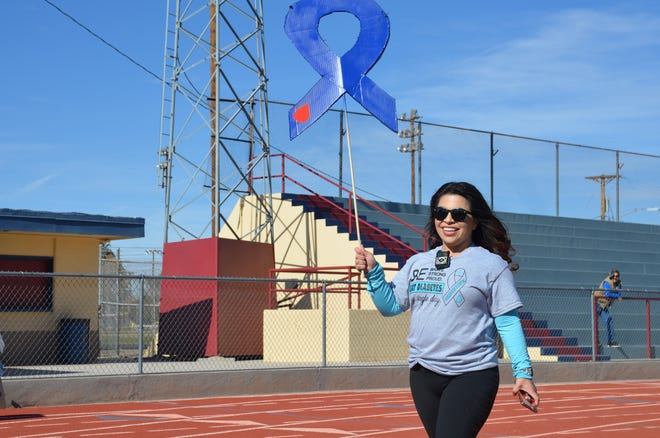 Johanna Quintana, organizer of Luna County Fight Diabetes 2-mile walk proudly walks with her blue ribbon placard.