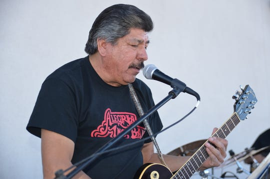 Joe Luera, guitarist of the Alegria Band performing in front of attendees of Luna County Coats for Kids drive.