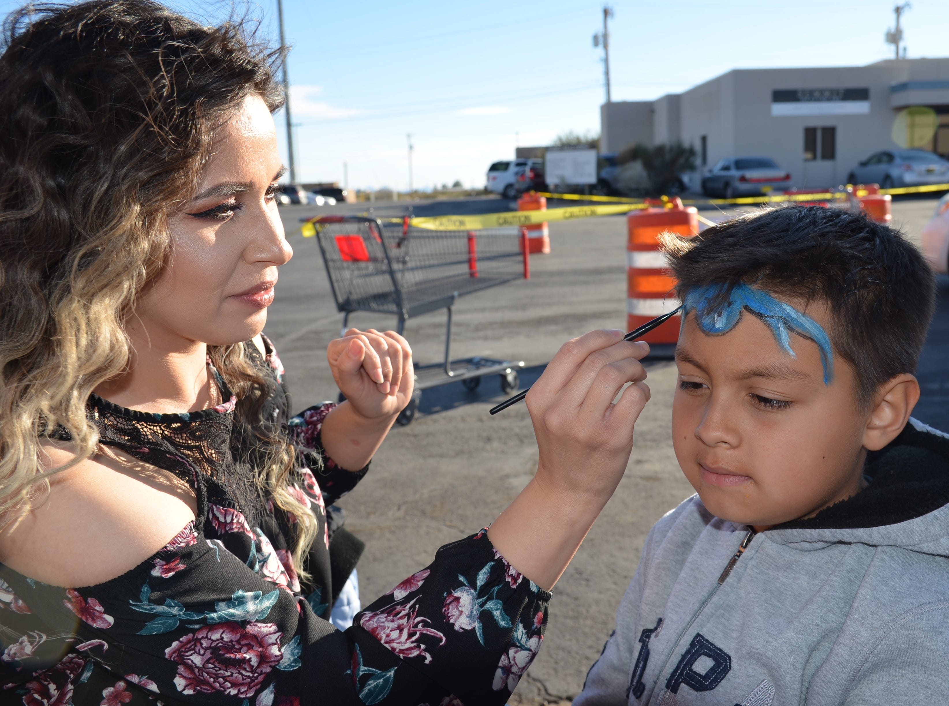 Help NM Teacher Jessica Lopez paints an octopus on the face of eight-year-old Xzavier Yates of Silver City, New Mexico.