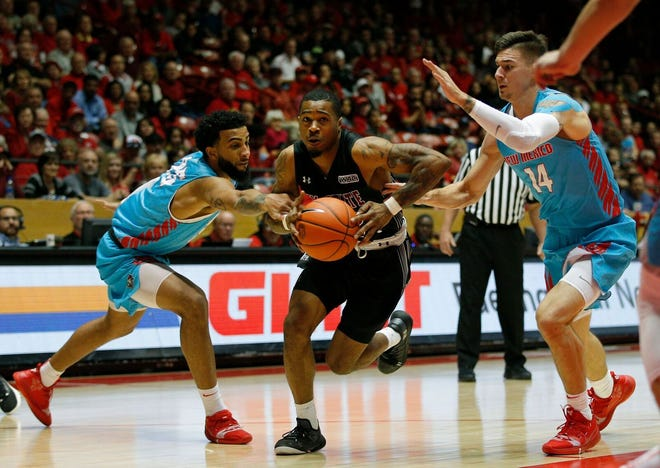 New Mexico State's AJ Harris drives to the basket against New Mexico on Saturday at The Pit.