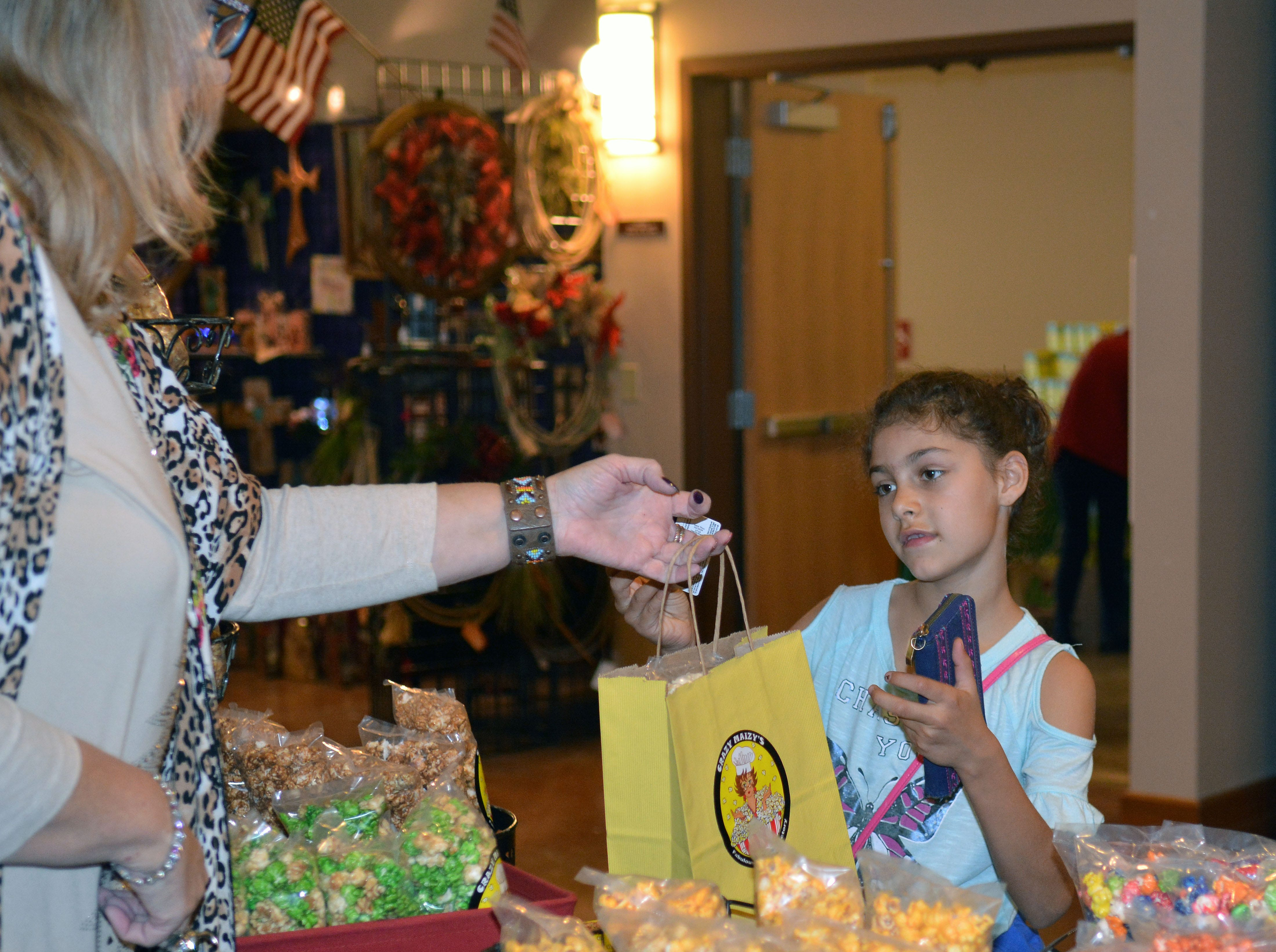 Eight-year-old Persephonie Cullins makes a popcorn purchase from Crazy Maizy's during Saturday's HomeGrown event at the Farm & Ranch Heritage Museum.   Photo taken 11/17/18.
