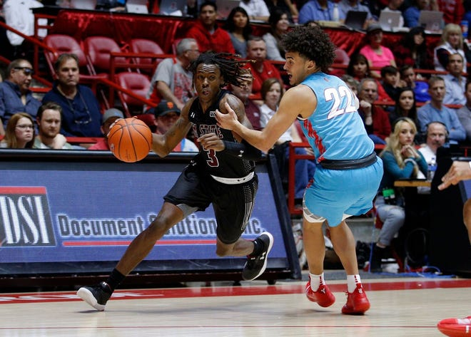 New Mexico State's Terrell Brown looks to get around New Mexico's Drue Drinnon at The Pit in Albuquerque on Saturday.