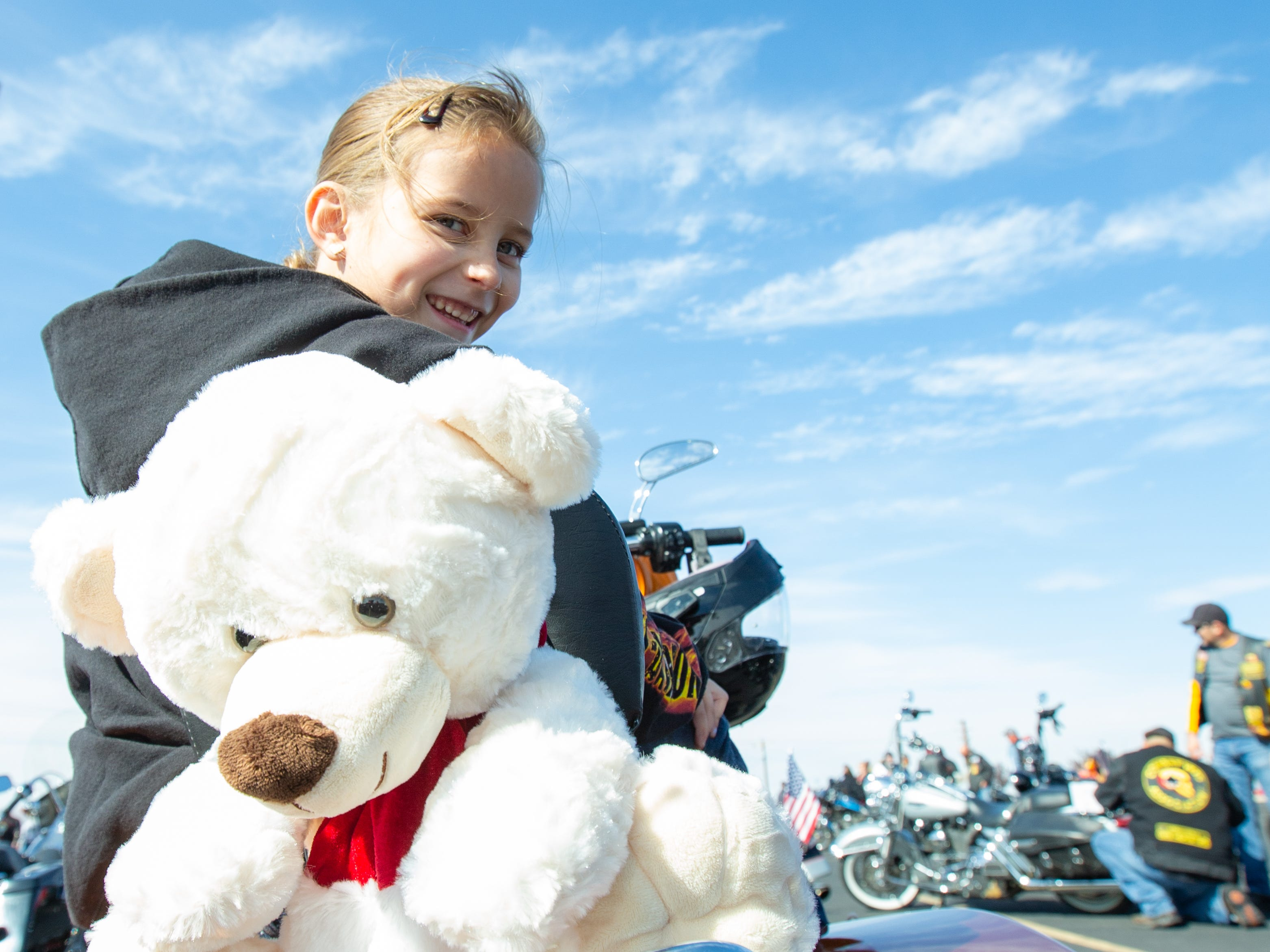 Aubrie Lucero, of Fredericksburg, Texas, hangs out on her father's bike with a stuffed animal  as they participate in the 38th annual Toys for Kids Motorcycle Parade to benefit children in southern New Mexico.