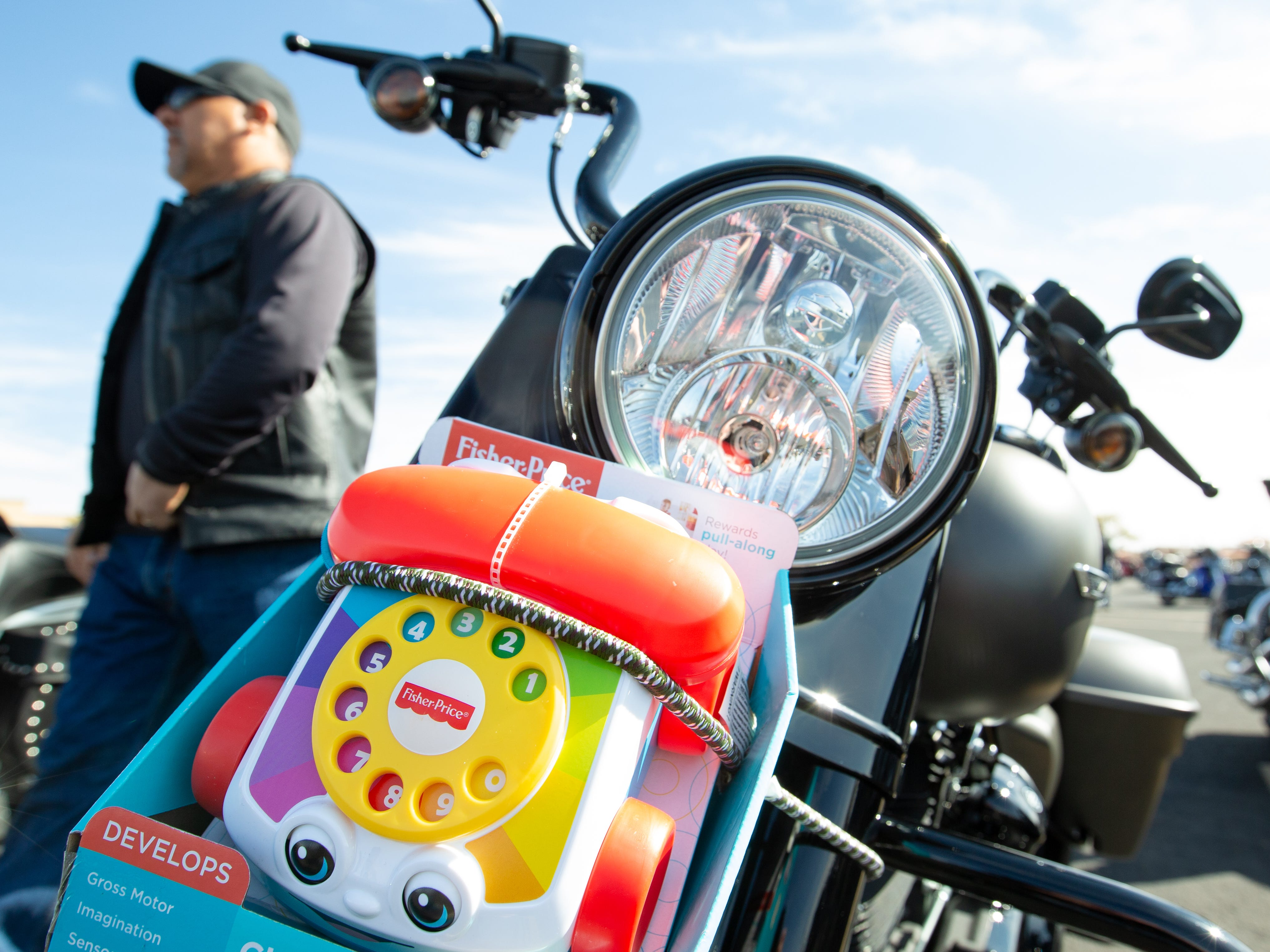 A toy is strapped to the front of a bike on Sunday Nov. 18, 2018, during the 38th annual Toys for Kids Motorcycle Parade to benefit children in southern New Mexico. Hundreds of motorcyclist participated in the event. Al Marrujo, of Las Cruces, is pictured walking in the background.