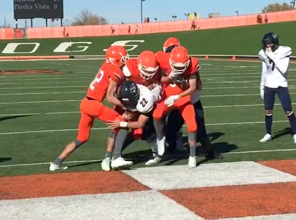 Piedra Vista's Mckay Cook (22) drags a few Artesia defenders in for a touchdown in the first half of Saturday's Class 5A quarterfinals.