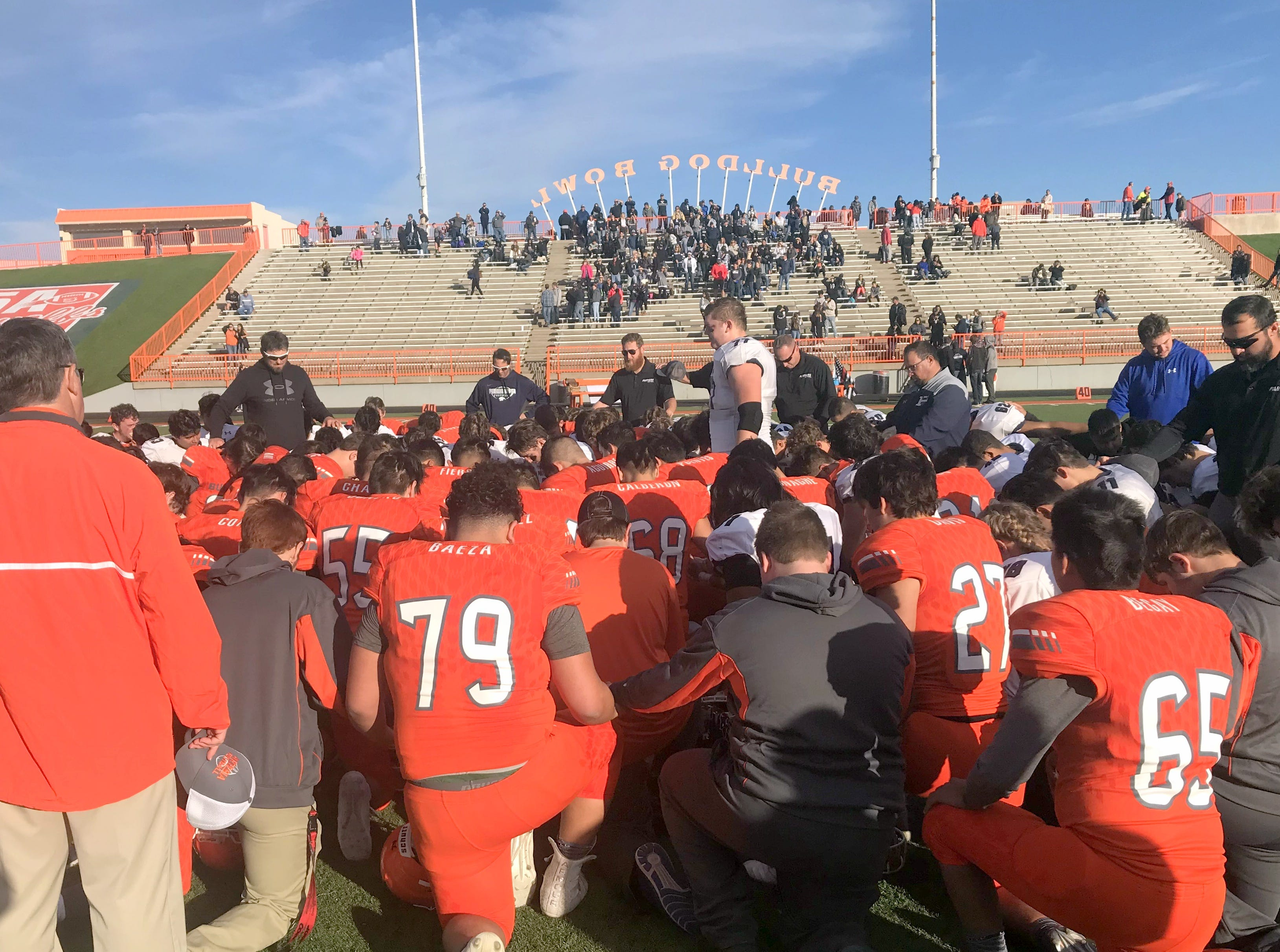 Piedra Vista's Benjamin Rasmussen (77) leads Artesia and Piedra Vista in a team prayer after Saturday's Class 5A quarterfinals.