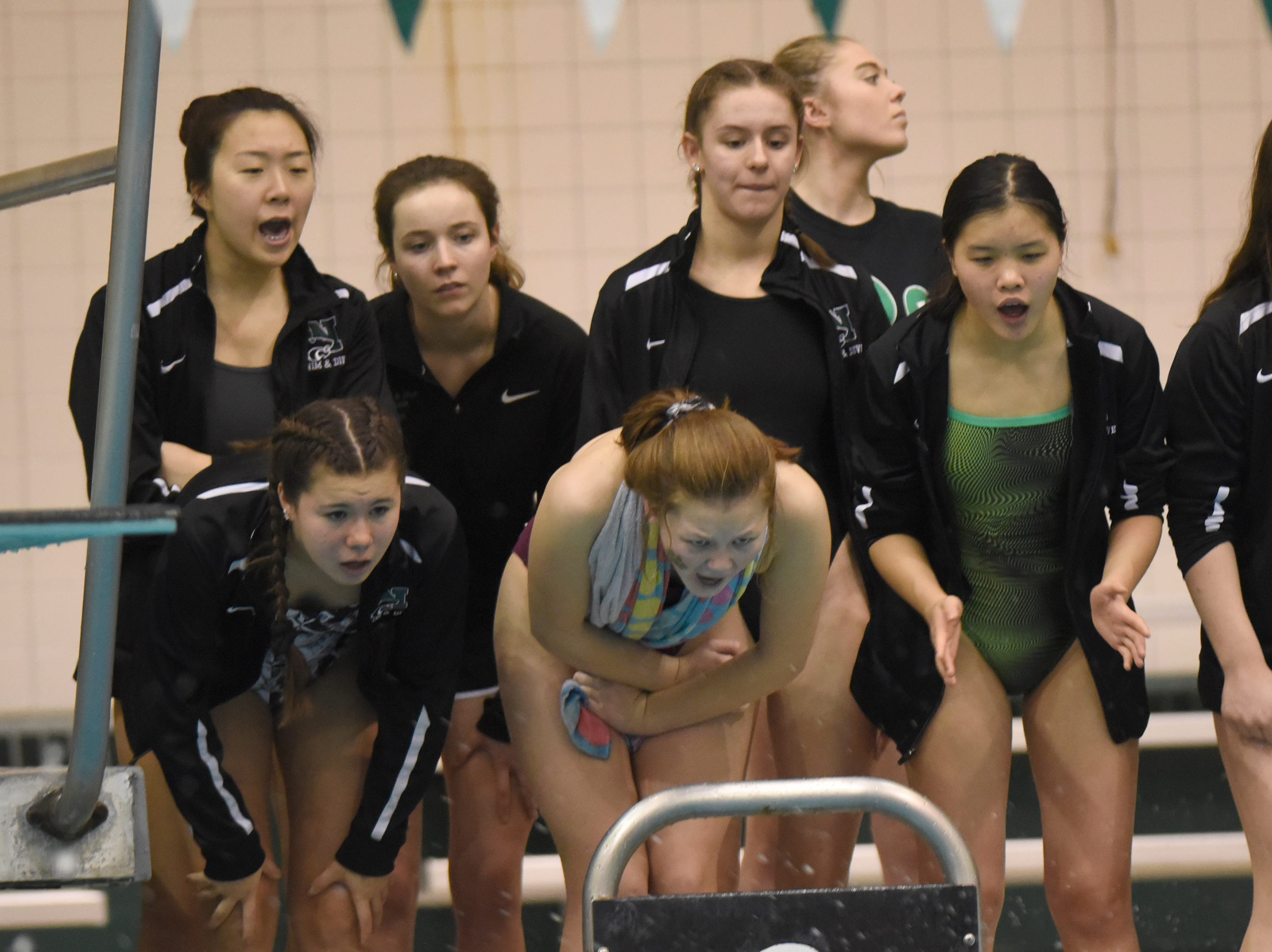 Novi swimmers cheer on their 400 yard freestyle relay team at the Division 1 girls swimming and diving championships held at Eastern Michigan University Nov. 17, 2018.