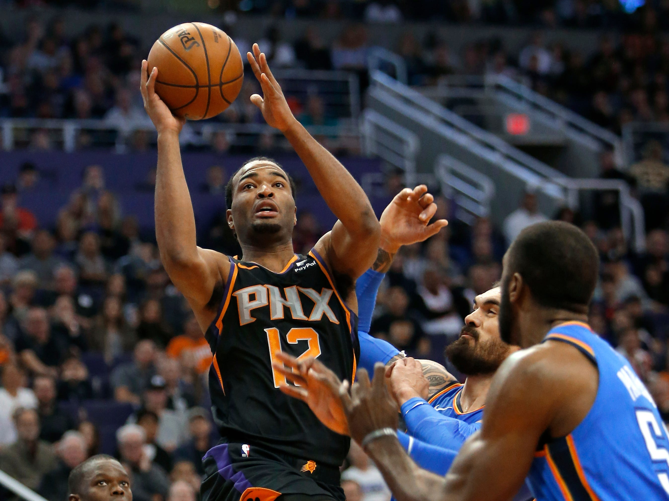 Phoenix Suns forward TJ Warren (12) drives between Oklahoma City Thunder's Steven Adams and Patrick Patterson (54) during the first half of an NBA basketball game Saturday, Nov. 17, 2018, in Phoenix. (AP Photo/Rick Scuteri)